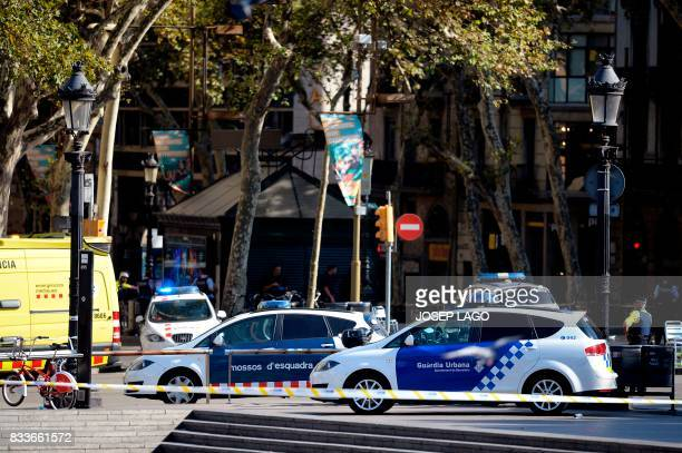 TOPSHOT Policemen stand next to vehicles in a cordoned off area after a van ploughed into the crowd injuring several persons on the Rambla in...