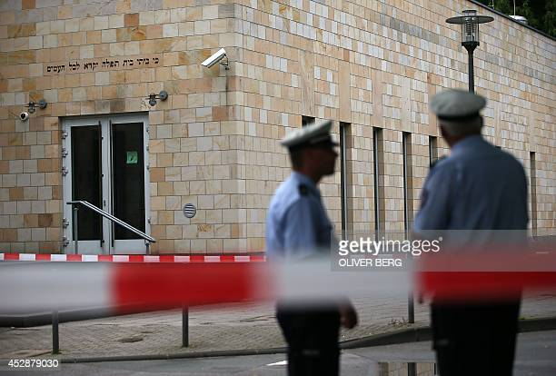 Policemen stand on July 29 2014 outside a synagogue in Wuppertal western Germany where three men tried to commit an arson attack by throwing several...