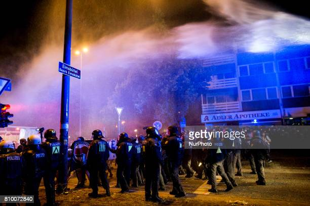 Policemen stand under a spray of a water gun in Hamburg Germany on July 6 2017 The police stopped the leftradical demonstration quotG20 Welcome to...