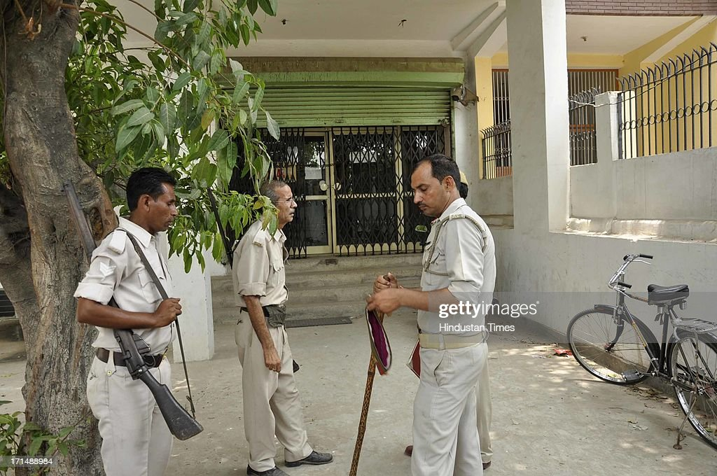 Policemen standing in front of Oriental Bank of Commerce branch where a businessman was robbed of Rs 23.5 lakh at gun point by two bike-borne armed assailants in Sahibabad area on June 25, 2013 in Ghaziabad, India.