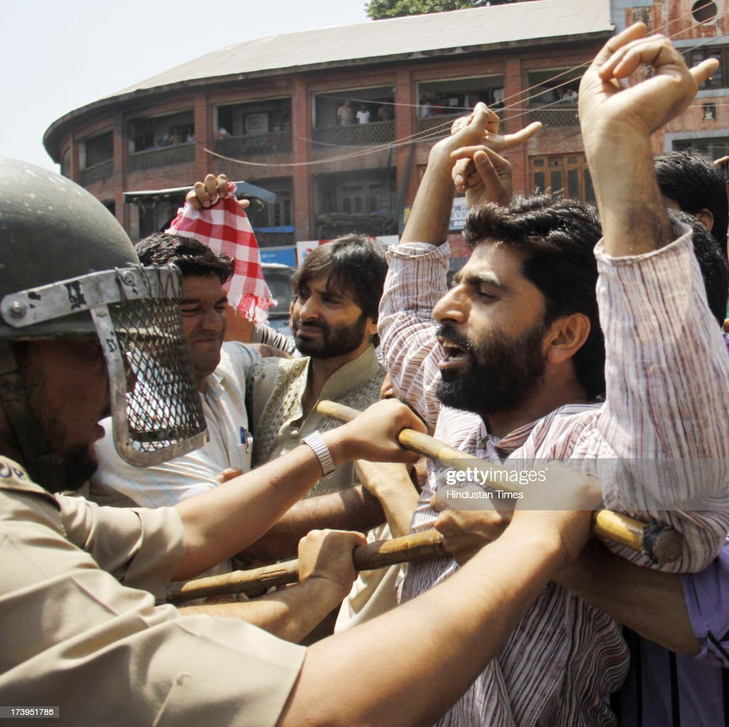 Policemen stop supporters of Jammu Kashmir Liberation Front during a protest against killing of 4 people in BSF firing on July 18, 2013 in Srinagar, India. Four people were killed today when security personnel opened fire at a mob that had gathered at a BSF camp in Ramban district protesting against alleged manhandling of an Imam of the area by the force. Curfew would be imposed in Srinagar and all other major towns in the Kashmir Valley from Friday morning as a precautionary measure.