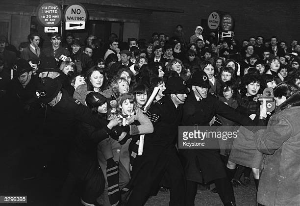 Policemen struggle to control an excited crowd of young female Beatles fans