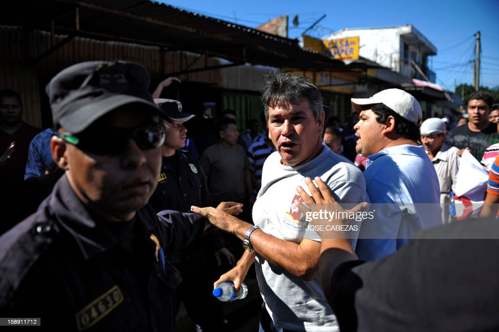 Policemen surround a group of bus drivers as they protest in San Salvador, on January 3, 2013. Bus owners and drivers called for a strike in demand of a rise in the price of the ticket for the buses of public transportation. AFP PHOTO/ Jose CABEZAS
