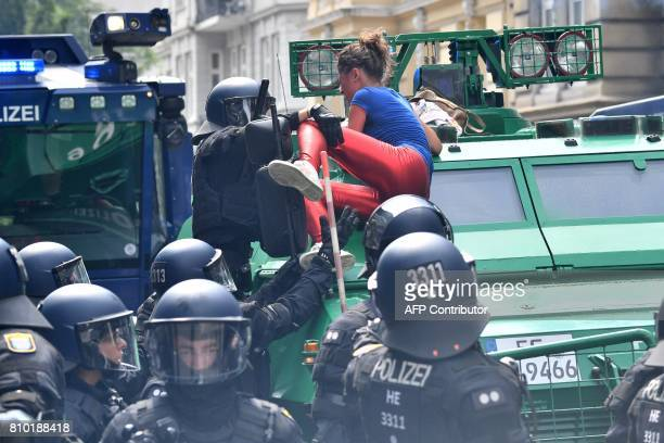 Policemen take away a demonstrator who has climbed onto an armored vehicle of the police during a protest on July 7 2017 in Hamburg northern Germany...