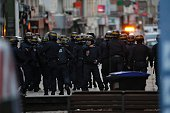 Policemen take combat position in the northern Paris suburb of SaintDenis city center on November 18 as French Police special forces raid an...