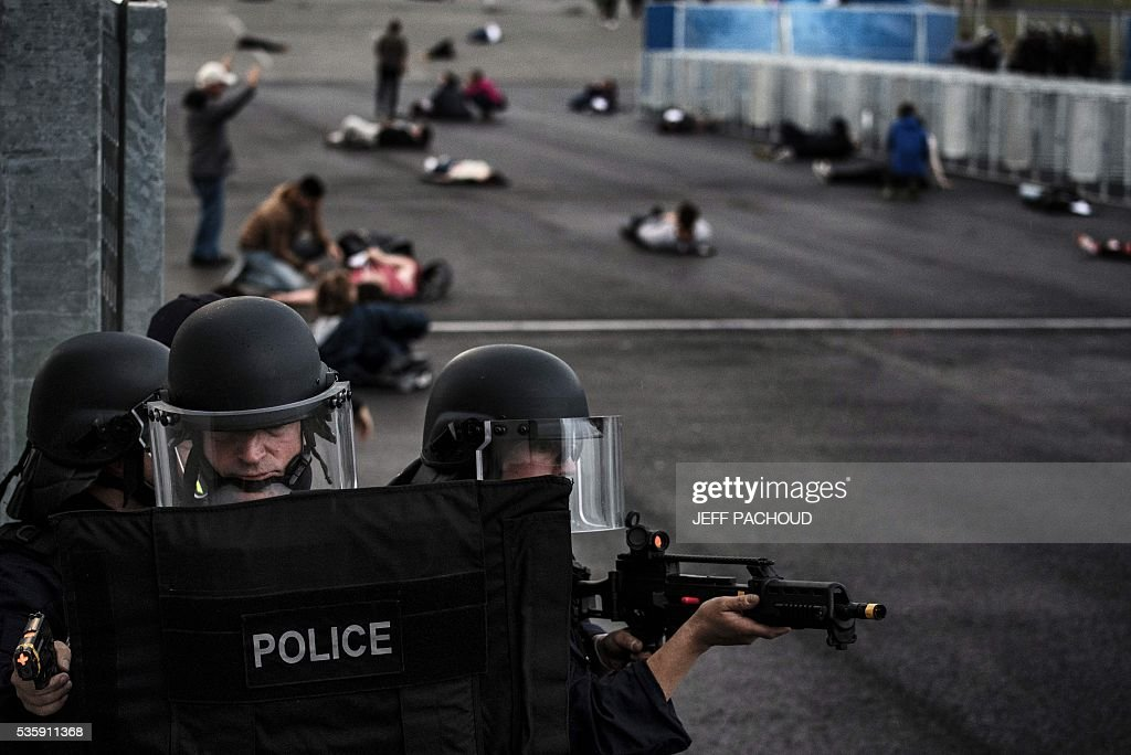 Policemen take part in a mock suicide attack exercise as part of security measures for the upcoming Euro 2016 football championship, at the Parc Olympique Lyonnais stadium in Decines-Charpieu, near Lyon, central-eastern France, on May 30, 2016. / AFP / JEFF