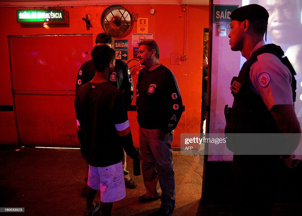 Policemen talk to a minor that was in a nightclub during an inspection in a suburb of Brasilia, on February 2, 2013. The Brazilian authorities ordered the inspection of many bars and nightclubs all over the country after the blaze in the Kiss Nightclub in Santa Maria, southern Brazil, that left more than 230 people dead. AFP PHOTO/ Pedro LADEIRA