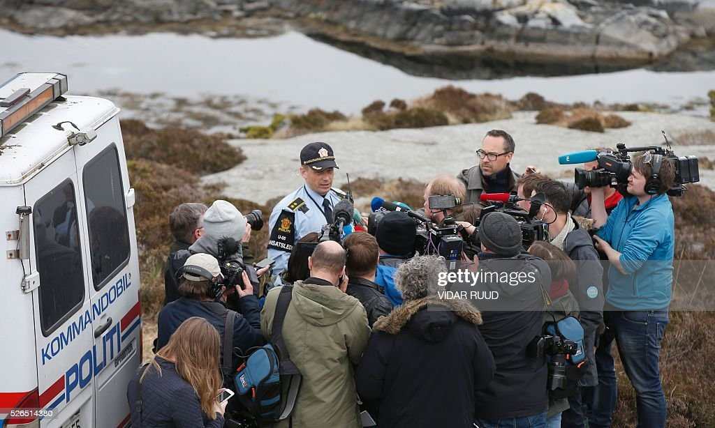 A Policemen talks to media during an inspection of the area where a helicopter crashed on April 29th on the island Turoy otside of Bergen on April 30, 2016. All 13 people on board a helicopter that crashed off the coast of western Norway died in the accident, rescue services said. / AFP / NTB scanpix AND NTB Scanpix / Vidar Ruud / Norway OUT