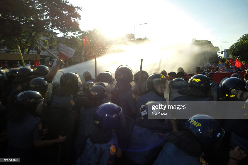 Policemen train a water cannon to protesters attempting to march towards the US Embassy during a rally commemorating Labor Day in Manila on Sunday, May 1, 2016. Thousands of protesters marched to protest the government's labour policy and demand higher wages amid rising prices for basic commodities.