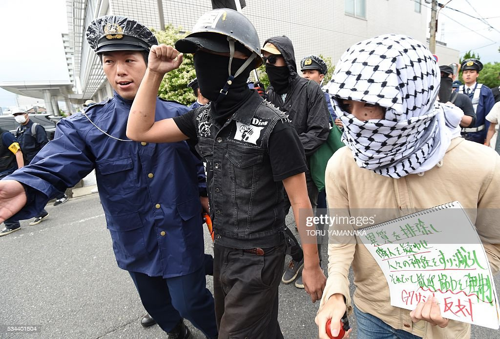 Policemen try to control people during a demonstration denouncing the Group of Seven (G7) summit meeting in Tsu, Mie prefecture, on May 26, 2016. Japan is on high-alert ahead of a Group of Seven summit with thousands of police on the streets of Tokyo and fanning out across the country as authorities boost security to unprecedented levels. / AFP / TORU