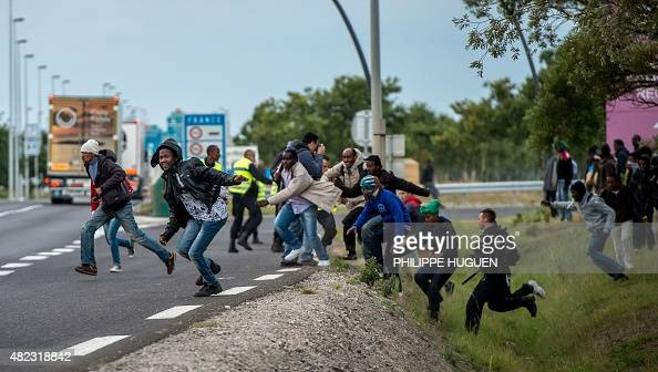 Policemen try to prevent migrants from reaching the Channel Tunnel operated by Eurotunnel in Coquelles near Calais northern France on late July 29...
