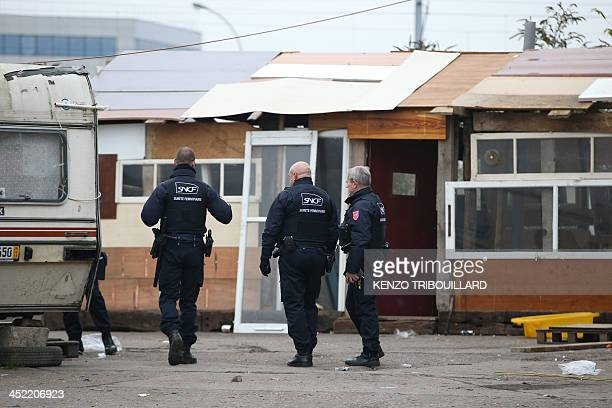 Policemen walk in a camp where some 800 people of the Roma community were living following its evacuation by policemen on November 27 2013 in...