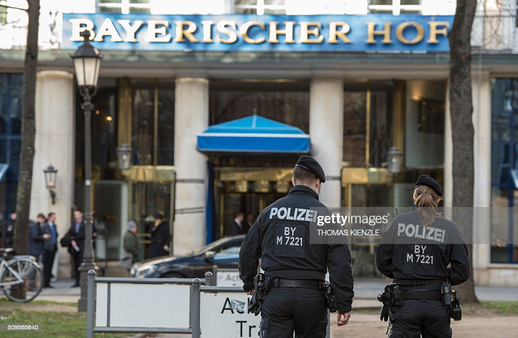 Policemen walk in front of the Bayerischer Hof hotel, the location for the 52nd Munich Security Conference (MSC), in Munich, southern Germany, on February 11, 2016. The Munich Security Conference takes place from February 12 und until February 14, 2016. / AFP / THOMAS KIENZLE