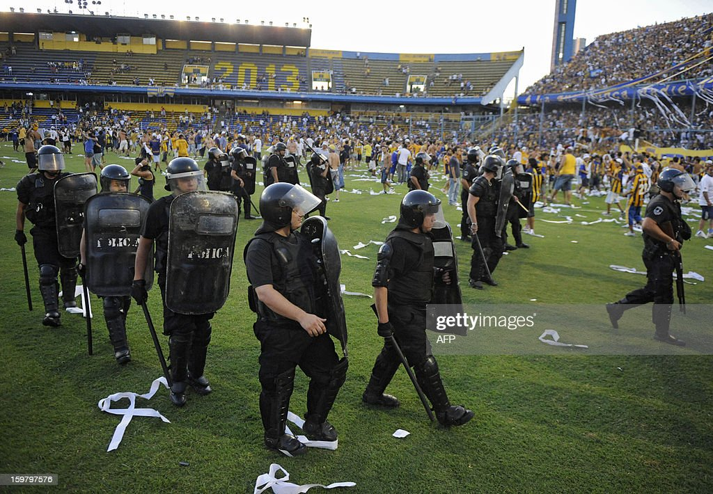 Policemen walk on the field before the Argentinian football match between Newells' Old Boys and Rosario Central at 'Gigante de Arroyito' stadium in Rosario, Argentina on January 20, 2013. The match was suspended due to disturbs.