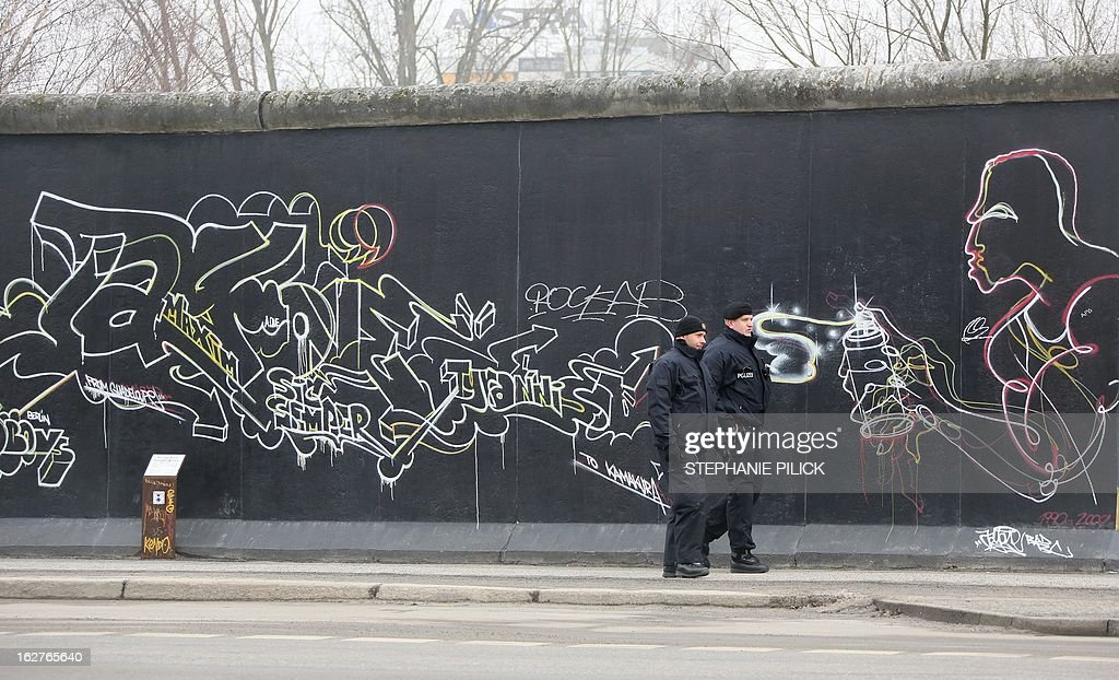 Policemen walk past a part of the so called East Side Gallery in Berlin on February 26, 2013. The group 'Mediaspree versenken!' (Sink Mediaspree!), members of local action groups and a commission of clubs neighbouring the Spree border at the former Berlin Wall's death zone are protesting against the planned demolition of parts of the East Side Gallery in order to construct luxury appartments. The East Side Gallery stretch of the Berlin Wall was taken over by artists who decorated the yet untouchable east side with artwork and political statements, after the wall was taken down in 1989-1990. AFP PHOTO / STEPHANIE PILICK GERMANY OUT