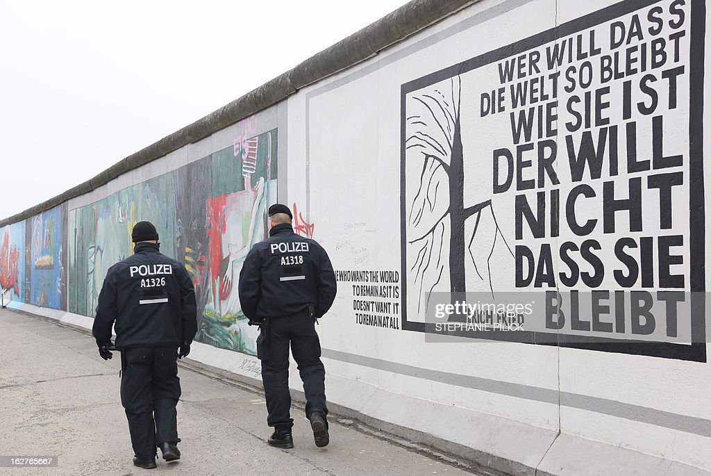 Policemen walk past a part of the so called East Side Gallery in Berlin on February 26, 2013. The group 'Mediaspree versenken!' (Sink Mediaspree!), members of local action groups and a commission of clubs neighbouring the Spree border at the former Berlin Wall's death zone are protesting against the planned demolition of parts of the East Side Gallery in order to construct luxury appartments. The East Side Gallery stretch of the Berlin Wall was taken over by artists who decorated the yet untouchable east side with artwork and political statements, after the wall was taken down in 1989-1990.