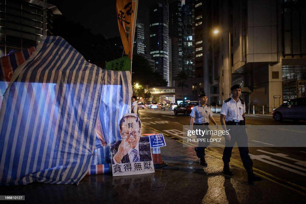 Policemen walk past a portrait of tycoon Li Ka-shing displayed next to the camp of dockers asking for an increase in pay and better working conditions, outside the headquarters of Asia's richest man in Hong Kong on late April 17, 2013. The International Terminals (HIT) which operates 12 berths, is a unit of tycoon Li Ka-shing's Hutchison Port Holdings Trust -- part of the vast empire owned by Asia's richest man whose firms control about 70 percent of the in the city's port traffic. AFP PHOTO / Philippe Lopez