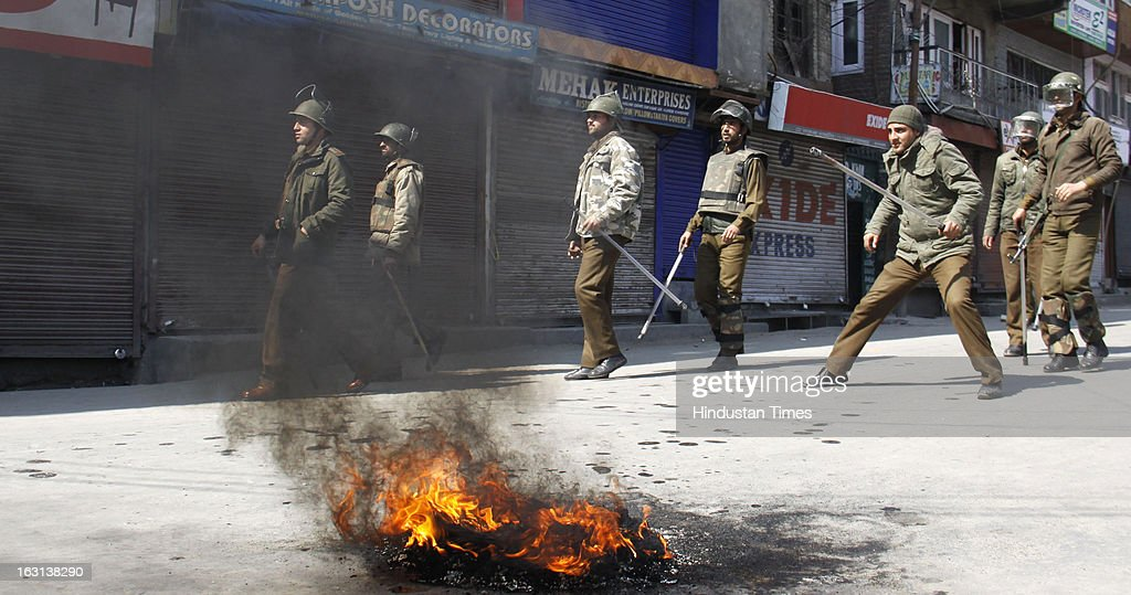 Policemen walk past burning tyres during a strike to protest the death of 28 year old Kashmiri student, Mudassir Qamran Malla in the city of Hyderabad on March 5, 2013 in Srinagar, India. Most shops, business establishments remained closed in Kashmir valley.