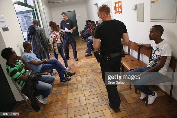 Policemen walk past migrants mostly from Pakistan and Eritrea waiting to have their photograph taken and fingerprints scanned as part of the...
