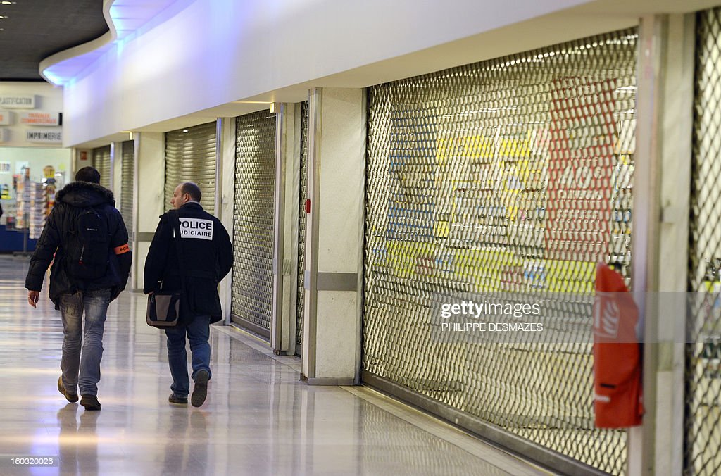 Policemen walk toward a supermaket where a woman had her throat cut by a man who ran away, on January 29, 2013 in La Ricamarie, central France. AFP PHOTO PHILIPPE DESMAZES