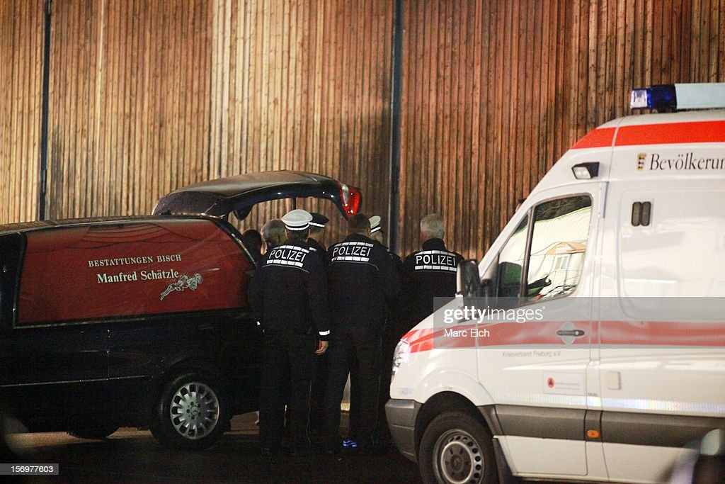 Policemen watch as one of the victims is taken away at the Caritas employment facility for the handicapped in which 14 people died in a fire on November 26, 2012 in Titisee-Neustadt, Germany. The fire was reportedly caused by an explosion at the facility, where approximately 120 people with disabilities are employed in light manufacturing.