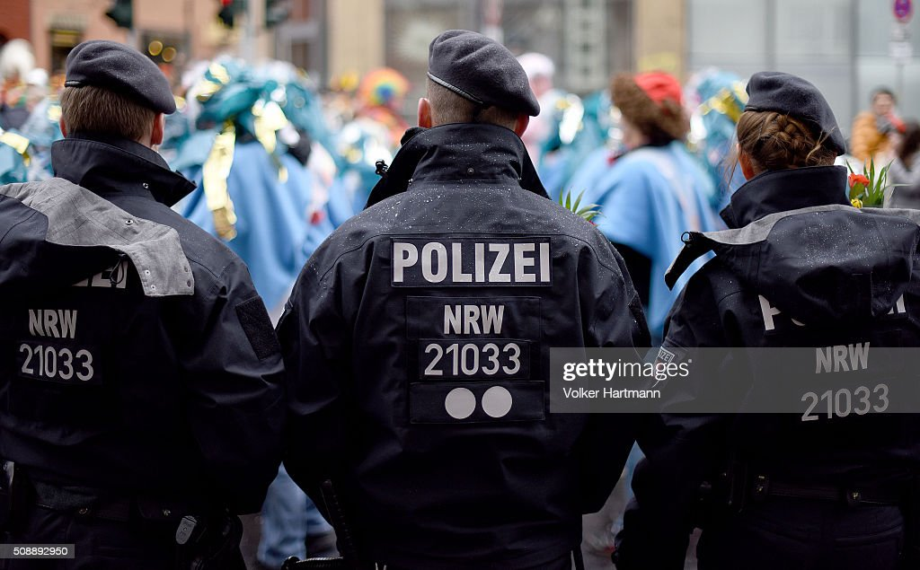 Policemen watch Carnival revellers during a carnival parade called 'Schull- un Veedelszoech' as part of the carnival season on February 7, 2016 in Cologne, Germany. Carnival partying and parades, a centuries-old tradition in western and southwestern Germany, traditionally occurs in February and runs until Ash Wednesday, the start of Lent, and culminates in Rose Monday parades and festivities. Police are on added alert this year, particularly in Cologne, due to the New Year`s Eve sex attacks on women that have been attributed to gangs of North African men, predominantly from Algeria and Morocco.