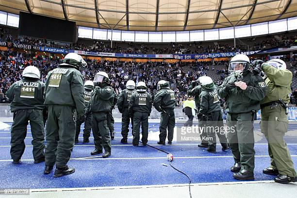 Policemen watch out for violent supporters of Berlin after the Bundesliga match between Hertha BSC Berlin and 1FC Nuernberg at Olympic Stadium on...