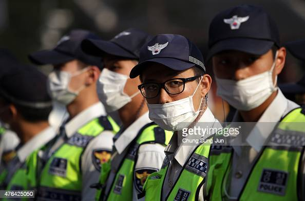 Policemen wear masks as a precaution to protect them against the MERS virus at Myeongdong shopping district on June 9 2015 in Seoul South Korea South...