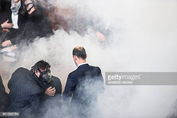 A policemen wearing a gas mask searches for tear gas canister as members of the Parliament stand in a cloud of a tear gas released by opposition...