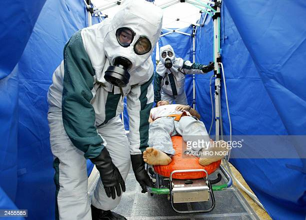 Policemen wearing antichemical and biological gear and a 'wounded' person from a damaged chemical truck wash at a improvised shower room during a...