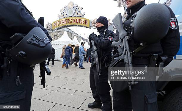 Policemen with machine guns stand at the entrance to a Christmas market in Hamburg northern Germany on December 20 as security measures are taken...