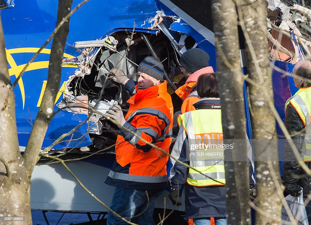 Policemen work at the site of a train accident near Bad Aibling, southern Germany, on February 12, 2016. German investigators try to determine what caused the train crash that killed 10 people, while media reports said that human error was to blame. Two trains travelling at high speed crashed head-on February 9, 2016, in one of Germany's deadliest accidents in years, with one slicing the other apart, ripping a large gash in its side. / AFP / dpa / Peter Kneffel / Germany OUT