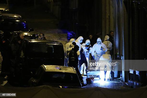 Policemen work into a marked out perimeter in Colline street in Verviers eastern Belgium on January 15 after two men were reportedly killed during an...