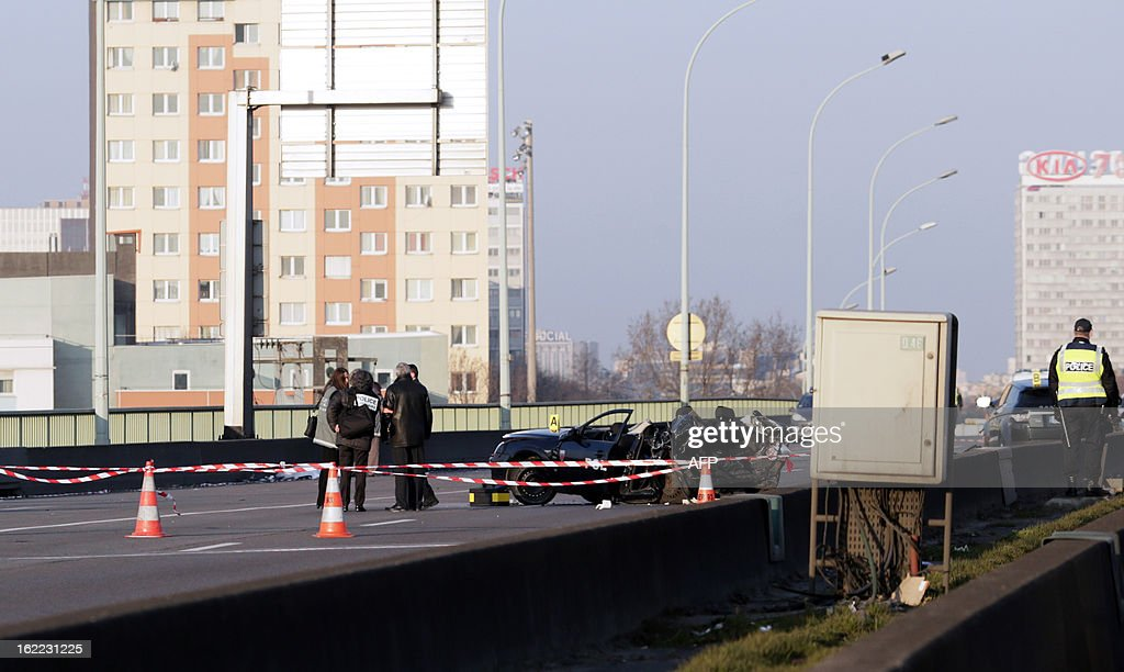 Policemen work next to a police car destroyed in a pursuit with a 4x4, killing two policemen on February 21, 2013 at the Porte de la Chapelle. AFP PHOTO KENZO TRIBOUILLARD