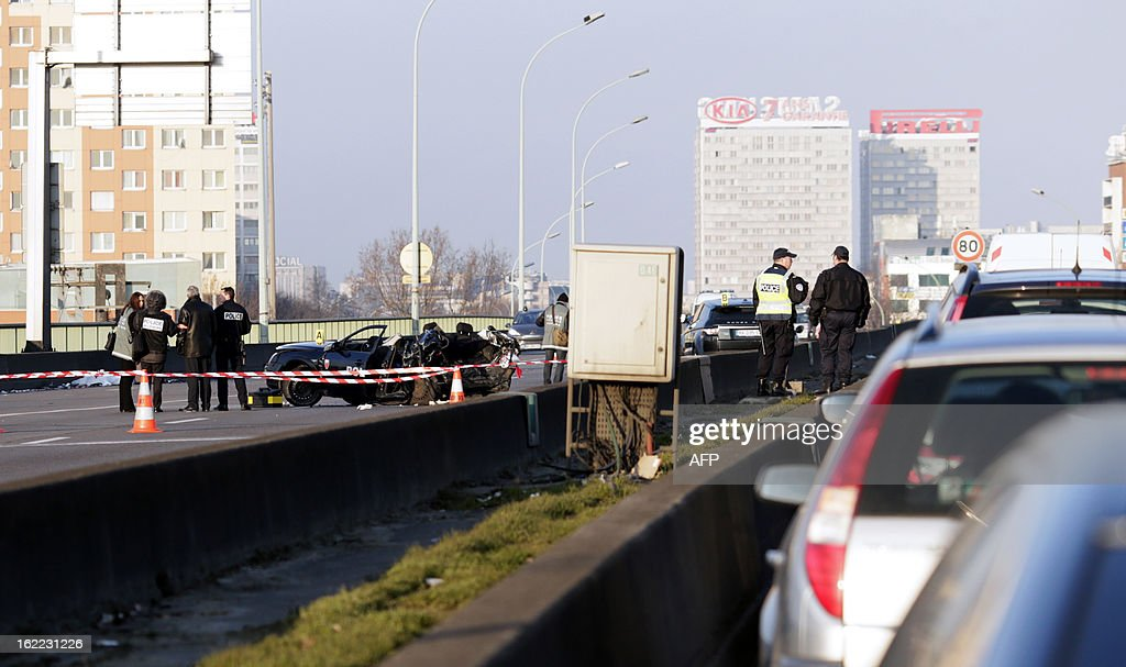 Policemen work next to a police car destroyed in a pursuit with a 4x4, killing two policemen on February 21, 2013 at the Porte de la Chapelle.