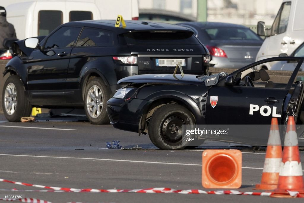 Policemen work next to a police car (R) destroyed in a pursuit with a 4x4 (L), killing two policemen on February 21, 2013 at the Porte de la Chapelle in Paris.