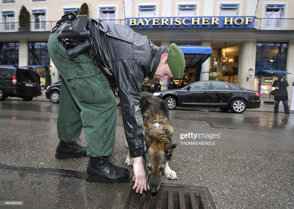 A policeofficer and his dog Dasko inspect a street drain in front of the Bayerischer Hof hotel in Munich, southern Germany, on February 1, 2013, where the 49th Munich Security Conference will start in the afternoon. The Munich Security Conference is to open with officials, ministers, top military brass and experts from 90 delegations discussing the world's hot button foreign policy issues at the three-day annual get-together. KIENZLE