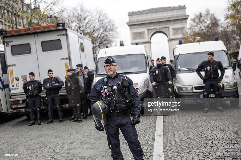 Polices stand guard a demonstration at the Avenue de la Grande Armee boulevard on December 12, 2015 in Paris, France. The final draft of a 195-nation landmark agreement on climate has been submitted at the United Nations conference on climate change COP21, aimed at limiting greenhouse gas emissions and keeping planetary warming below 2.0 degrees Celsius.