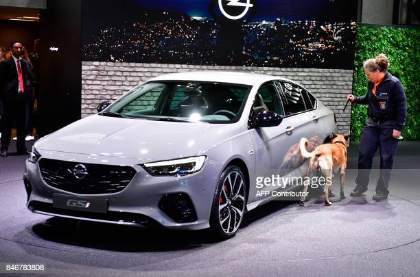 A policewoman and a sniffer dog inspect an Opel car prior to the visit of the German Chancellor at the booth of Opel during the official opening of...