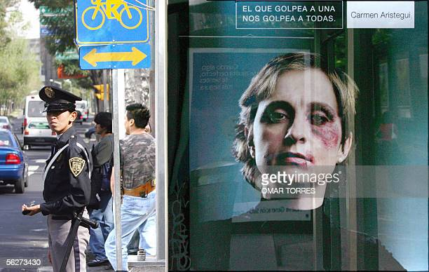 A policewoman controls the traffic in Mexico City close to a billboard with a picture of Mexican journalist Carmen Aristegui made up as if she had...