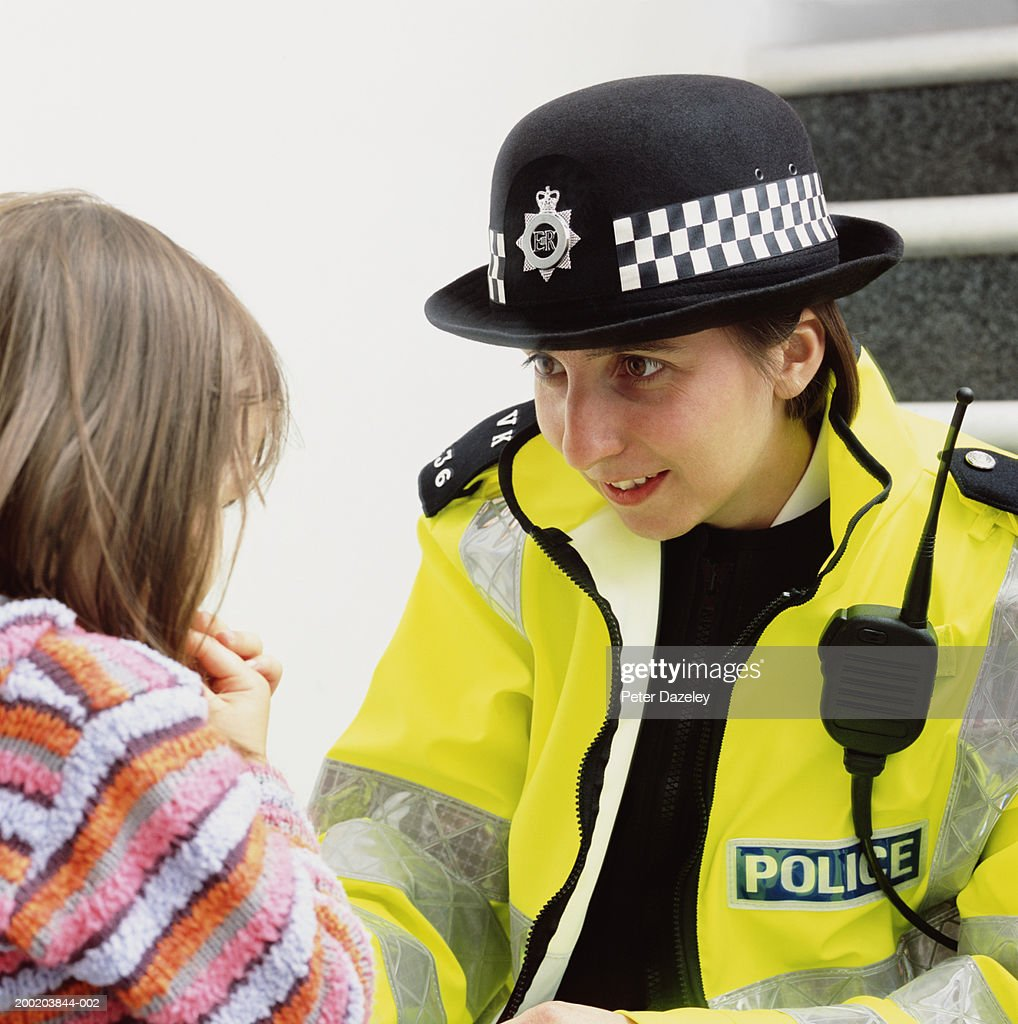 Policewoman crouching to talk to girl (3-5), close-up : Stock Photo