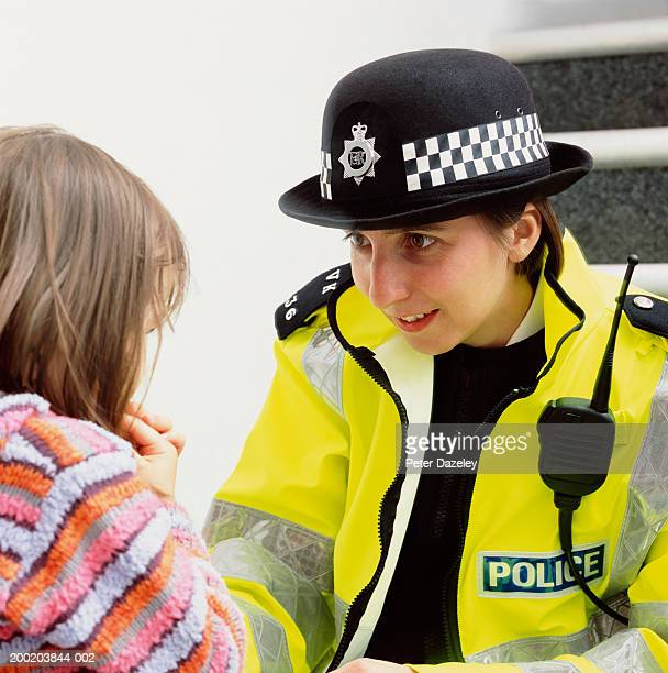 Policewoman crouching to talk to girl (3-5), close-up