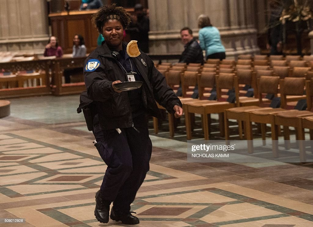 A policewoman flips a pancake during the Shrove Tuesday Pancake Race at the National Cathedral in Washington, DC, on February 9, 2016. Shrove Tuesday, also known as Mardi Gras, precedes Ash Wednesday, the first day of Lent. / AFP / Nicholas Kamm