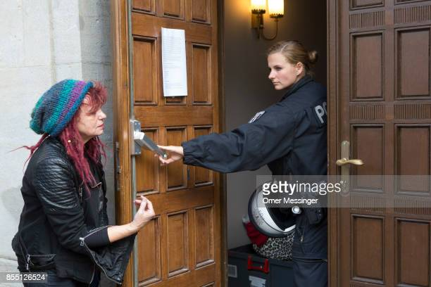 A policewoman is seen guarding the entrance of the Volksbuehne theater during negotiations to end the occupation of parts of the theater by activists...
