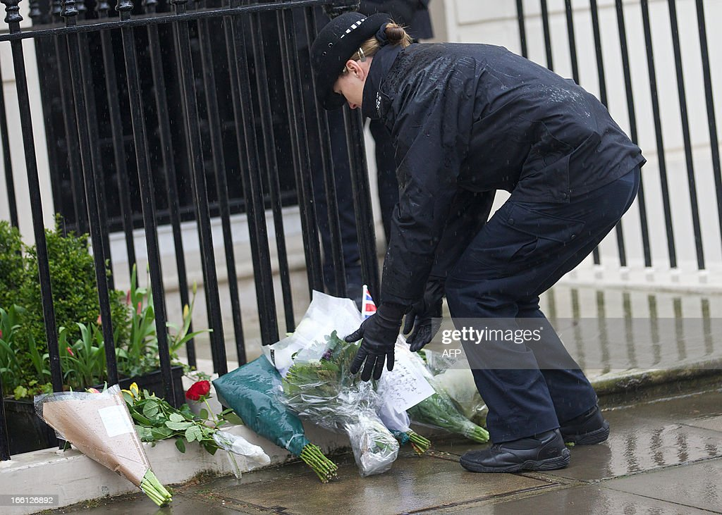 A policewoman lays floral tributes on behalf of members of the public outside the home of former British Prime Minister Margaret Thatcher in London, on April 9, 2013. Mikhail Gorbachev, Helmut Kohl and Bill Clinton were among the former friends and foes who joined in tributes to Margaret Thatcher, praising the fearlessness and fierce determination of an 'iconic' leader.