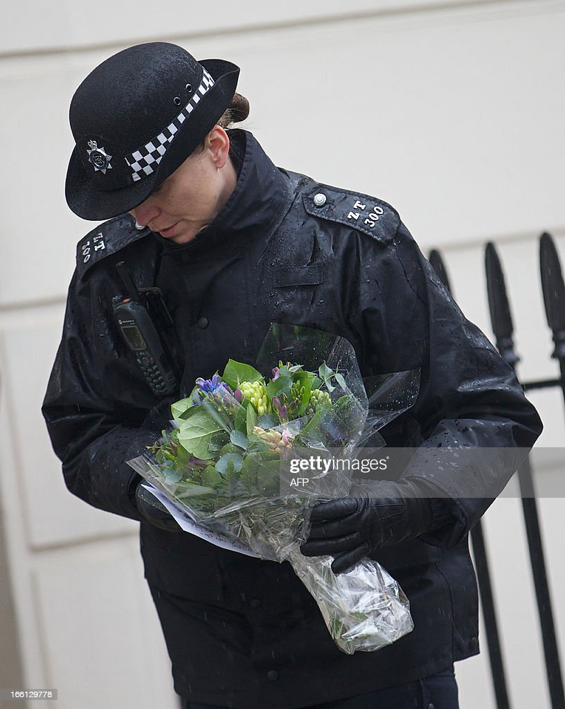 A policewoman lays floral tributes on behalf of members of the public outside the home of former British Prime Minister Margaret Thatcher in London, on April 9, 2013. Mikhail Gorbachev, Helmut Kohl and Bill Clinton were among the former friends and foes who joined in tributes to Margaret Thatcher, praising the fearlessness and fierce determination of an 'iconic' leader. AFP PHOTO / ANDREW COWIE