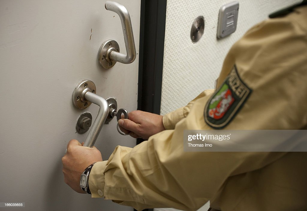 Policewoman locking the door of a private cell at the police headquarters of Hagen