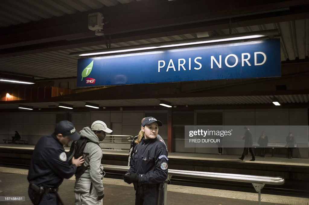A policewoman looks around while her colleague searches a man as they conduct an identity check on him in the Gare du Nord (North railway station) in Paris on November 30, 2012.