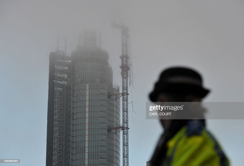 A policewoman looks at a damaged crane that was hit by a helicopter following the crash in central London on January 16, 2013. Two people were killed after a helicopter hit a crane at a building site and plunged to the ground in a ball of flames, police said.