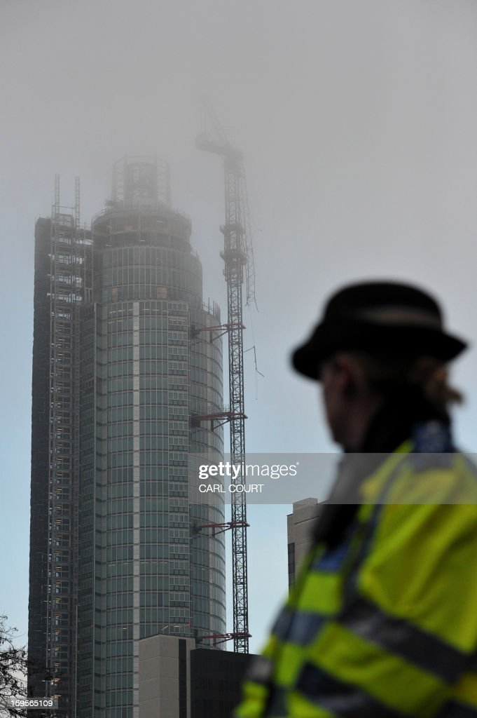 A policewoman looks at a damaged crane that was hit by a helicopter following the crash in central London on January 16, 2013. Two people were killed after a helicopter hit a crane at a building site and plunged to the ground in a ball of flames, police said. AFP PHOTO / CARL COURT